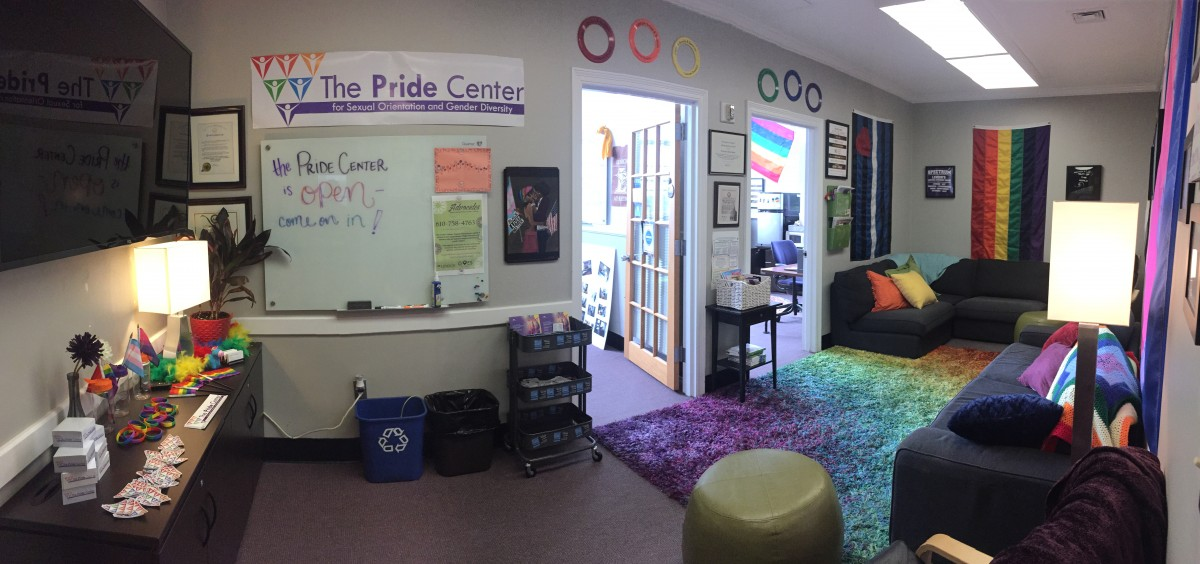 "Photo of the Pride Center Lounge, which includes LGBTQ+ flags, rainbow decorations, and a sign reading ""The Pride Center is Open! Come on in!"""