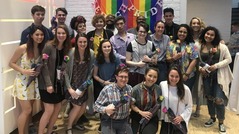 Take Pride 2019 graduates standing in front of Pride Flag and Lehigh Pride sign. Graduates are holding their rainbow roses received at the ceremony