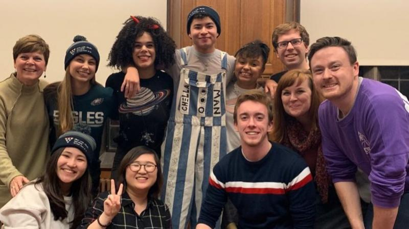 photo of pride center student staff with Chella Man for the Fall 2019 event Chat with Chella. Chella is wearing blue and white vertical striped overalls and a navy blue beanie.