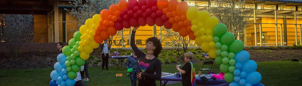 Student staffer, Laura, admiring the balloons at our annual Pride-a-Palooza event