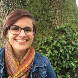 Photo of Leslie wearing a denim jacket with a multicolor scarf.